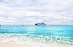Cruise ship and tender on a light blue sea at Half Moon Cay in t. He Bahamas under cloudy skies Stock Photos