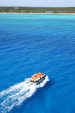 Cruise Ship Tender Run. A cruise ship tender shuttles passengers to a tropical island Stock Photos