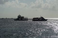 Cruise ship tenders in silhouette at Grand Cayman. Cruise ship tenders passing one another in the harbor, with both in silhouette, off the coast of Grand Cayman Stock Photos