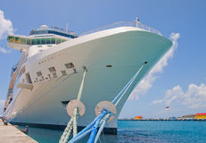 Cruise Ship Tied to Dock with Two Blue Ropes. A huge white luxury cruise ship tied to a tropical pier with two long blue ropes Royalty Free Stock Photography