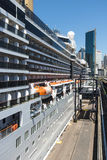 Cruise ship tied up to the wharf. Looking down the length of the he P&O Cruise ship Arcadia tied up at Circualr quay Sydney towering over the quay with the city Royalty Free Stock Photography