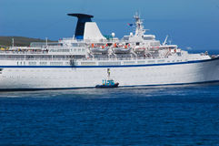 Cruise ship transfer. Cruise ship leaving and the harbour pilot transferring off onto the pilot vessel Stock Photo