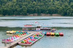 Cruise ship that transports people across the lake and many colorful pedal boats for people to enjoy,. Pretty boat for a cruise on the lake with some pedal boats stock photography