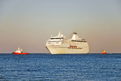 Cruise ship and two tugboats Stock Photography