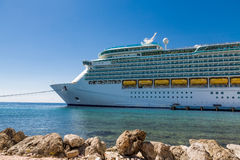 Cruise Ship Under Blue Beyond Rocks Royalty Free Stock Images