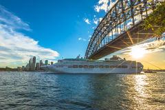 Cruise ship. Under Sydney Harbour Bridge at sunset with skyline, New South Wales, Australia