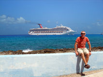 Cruise ship vacation. A man enjoys time in Grand Cayman with his cruise ship waiting in the background Stock Photo