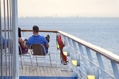 Cruise Ship Vacation. A couple enjoys relaxing on deck as their cruise ship leaves the Miami, Florida port Stock Photo
