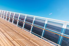 Cruise Ship Vacation Theme. Wooden Deck of the Cruise Vessel with Glassy Barriers and the Ocean Vista. Caribbean Vacation Time royalty free stock photos
