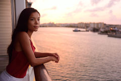 Cruise ship vacation woman enjoying balcony at sea. With beautiful sunset on travel at sea. Relaxed woman enjoying private balcony in stateroom. Asian Chinese Royalty Free Stock Photography