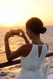 Cruise ship vacation woman taking photo with phone. Cruise ship vacation woman taking photo with smart phone camera enjoying sunset on travel at sea. Girl using Stock Photos