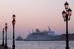 Cruise ship in Venice harbor at sunset. Delphin cruise ship in Venice harbor at sunset between lanterns Royalty Free Stock Images