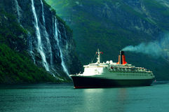 Cruise ship & waterfall. The famous Queen Elizabeth II cruise ship sailing in the ocean, along the Seven Sisters waterfall in Norway