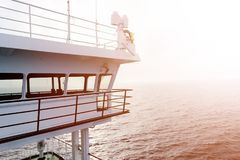 Cruise ship white cabin with big windows. Wing of running bridge of cruise liner. White cruise ship on a blue sky with radar and n. Avigation system. Captain`s Royalty Free Stock Photos