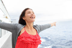 Cruise ship woman on boat in happy free pose. Smiling enjoying freedom. Young woman traveling on vacation travel sailing on open sea ocean. Young mixed race Royalty Free Stock Photo