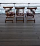 Cruise ship wooden deck chairs. Three Cruise ship wooden deck chairs over looking a quite sea Stock Images