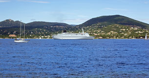 Cruise ship and yacht. Wide angle view of cruise liner ship and yacht in blue sea with shoreline in background stock image