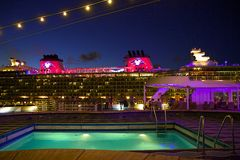 Cruise ships deck at night. Swimming pool at night with Disney cruise ship on background Stock Images