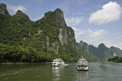 Cruise Ships on the Li River. Two cruise ships pass on the Li River in Southern China under the shadows of the remarkable karst limestone mountains Stock Images