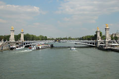 Cruise ships sailing under the bridge Alexandre III on the Seine river Royalty Free Stock Photos