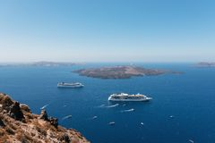 Cruise ships are staying moored in volcanic caldera of Santorini island, Greece.  stock images