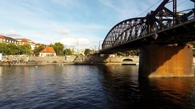 Cruise on the Vltava River in Prague,  Czech Republic,. A cruise boat passing under a railroad bridge on the Vltava River in Prague, Czech Republic stock video footage