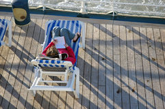 Cruise Writer. A young woman writes while resting on the rear deck of a cruise ship Stock Photography