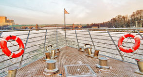 Cruise yaht sails on frozen river breaking the ice. Color winter photo. Royalty Free Stock Photo