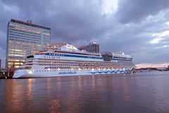 Cruiseboat in Amsterdam harbor in the Netherlands. Cruiseboat mooring in Amsterdam harbor  in the Netherlands at sunset Stock Photos