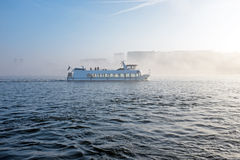 Cruiseboat in the fog in the harbor from Amsterdam the Nethe Royalty Free Stock Images