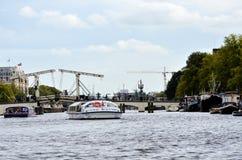 Cruiseboten in een kanaal in Amsterdam Stock Afbeelding
