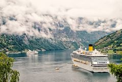 Cruiser ship in fjord, Norway.Luxury cruise ship at norwegian fjords. Cruiser ship or liner in fjord, bay or harbor, calm water surrounded by mountains on rocky royalty free stock photo