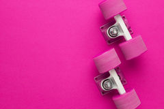 Cruiser skateboard trucks and wheels. On deep pink with background copy space Royalty Free Stock Photos