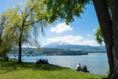Cruiser about to stop at quay to deliver tourists at park. May 5, 2017 - Lucerne, Switzerland: cruiser about to stop at quay to deliver tourists at park. People Stock Photo