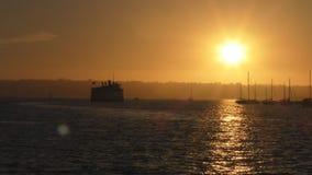 Cruiseschip in het overzees bij zonsondergang en jachten stock videobeelden