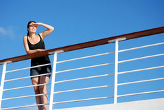 Cruising. Woman looking out over the railings of a cruise liner