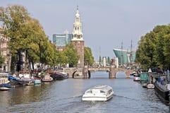 Cruising on Amsterdam channels in the Netherlands. Crossing the Montelbaanstoren Stock Photo
