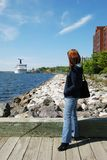 Cruising in Canada. The girl looking towards a cruise liner docked in Nova Scotia's town Sidney (Canada stock images