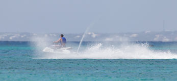 Cruising on the Caribbean Sea on a jet ski. Young guy cruising on the Caribbean Sea on a jet ski Stock Images