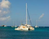 A cruising catamaran anchored in the grenadines Stock Photos