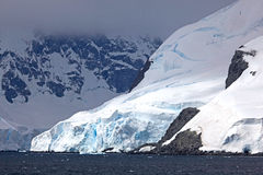 Cruising down the Gerlache Strait, Antarctica. Snow covered mountains with misty clouds above stock photos