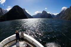Cruising through a fjord in Milford Sound, New Zealand. A couple on a boat enjoy the view from a boat in Milford Sound, New Zealand stock image