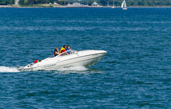 Cruising in a motor boat. Family in a fast power boat cruising on Lake Ontario along the shoreline stock photo