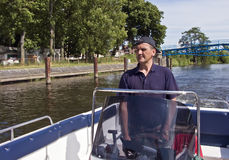 Cruising in motorboat. A man cruising along a river in a motorboat royalty free stock photography