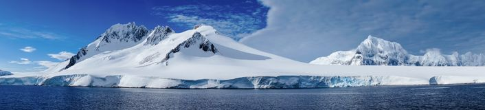 Cruising through the Neumayer channel with snow covered mountains in Antarctica. Cruising through the Neumayer channel full of Icebergs in Antarctica Royalty Free Stock Images