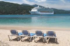 Cruising in Paradise. Cruise ship with four deck chairs in the foreground Stock Photography
