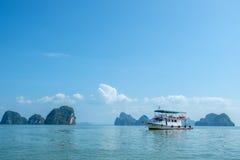 Cruising Phang Nga Bay in Thailand. Phang Nga Bay, Thailand – March 3, 2017: Tour boat among the scenic limestone islands in Phang Nga Bay. This is one of Royalty Free Stock Photo