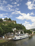 Cruising on the river in Germany. SAARBURG, GERMANY- August 4: Cruiseboat on the river Saar in Germany with medieval castle in Saarburg. River cruises in the Royalty Free Stock Photography