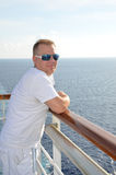 Cruising at Sea. Man stand on balcony over looking the ocean from a cruise ship. Vacation and relaxation time stock photo