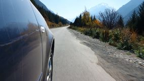 Cruising Up The Mountains. In this stock video, the closeup of wheels are shot as a vehicle plies a mountain road during the autumn season. This video can be stock video footage